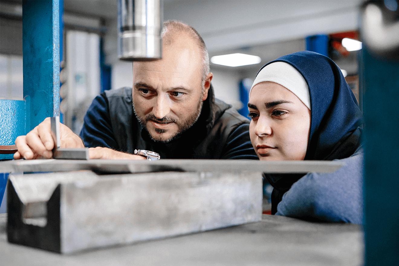 Ausbilder untersucht mit Schülerin Metallteile in Werkstatt